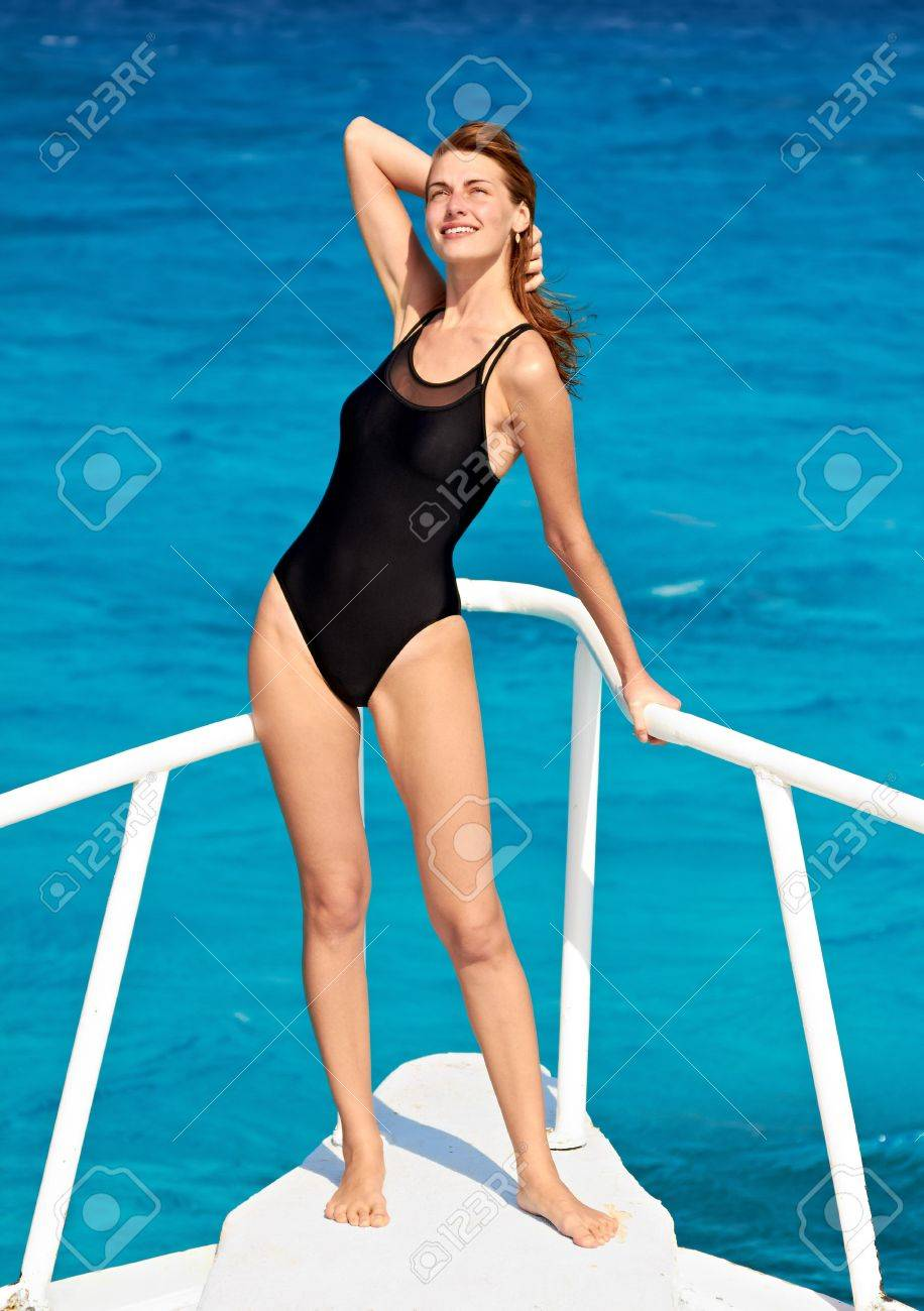 Young woman in swimsuit standing on yacht at sunny day Stock Photo - 12249164