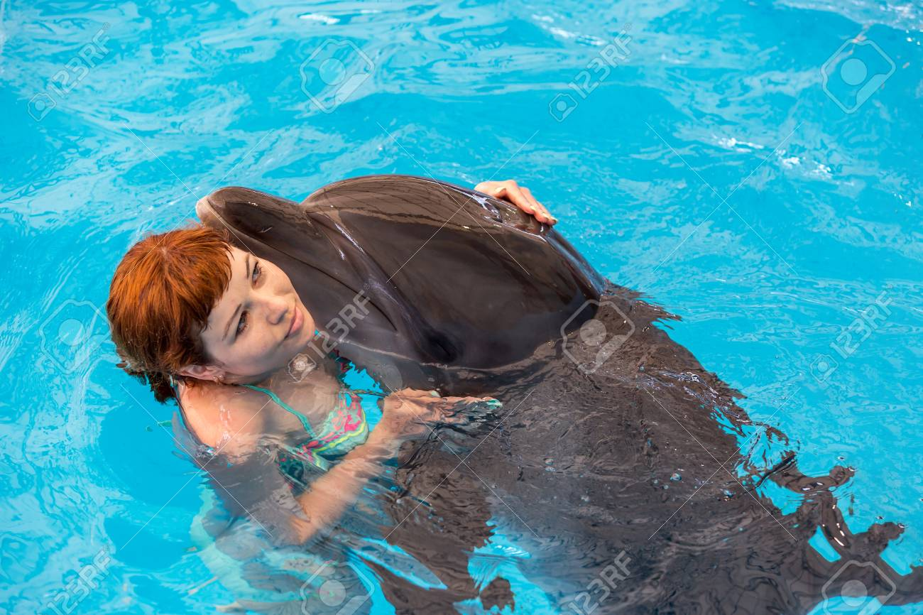 Young happy girl hugs with dolphin in swimming pool