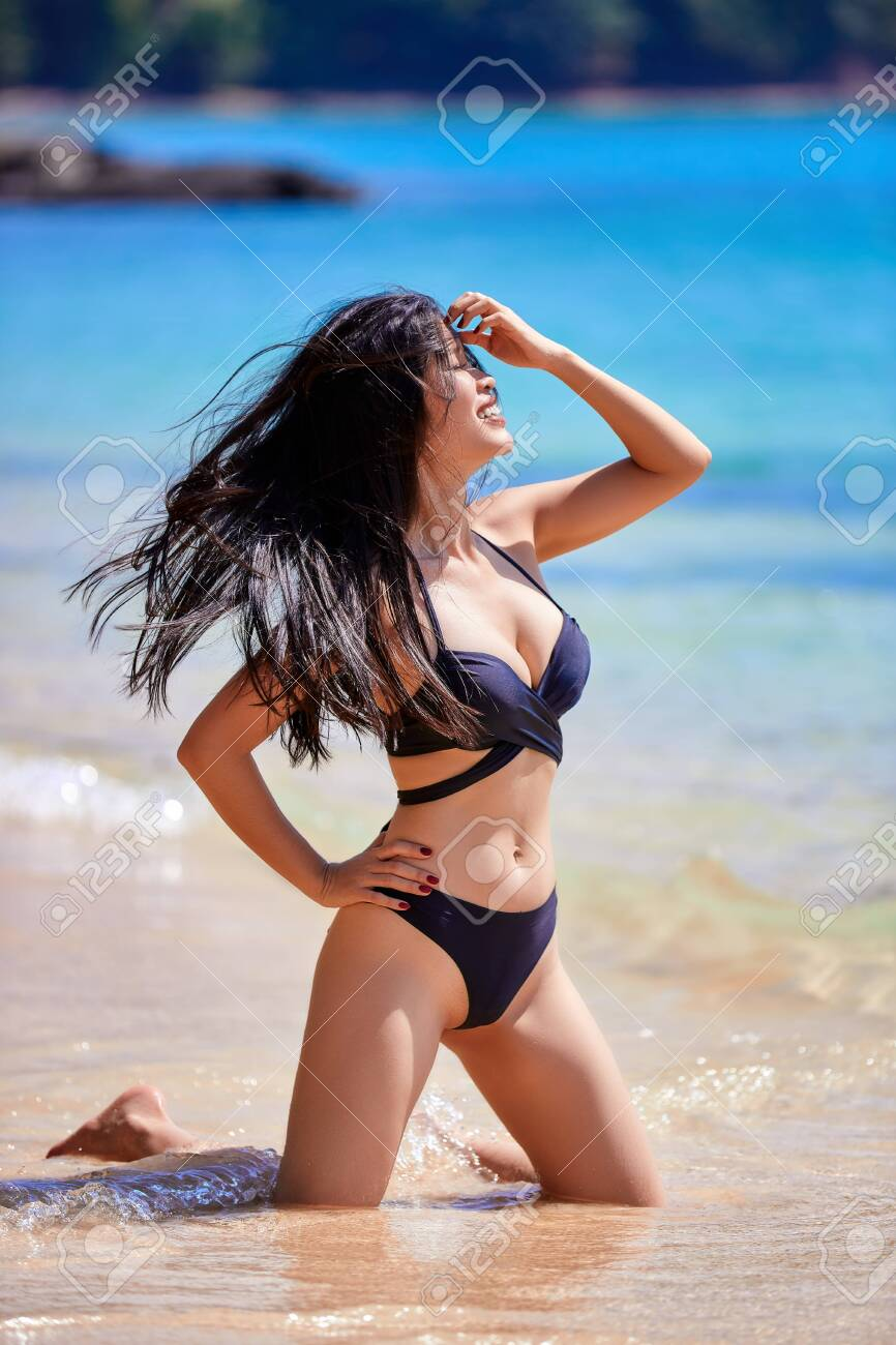 Beautiful asian woman enjoying on a tropical beach in a black swimsuit - 155702395