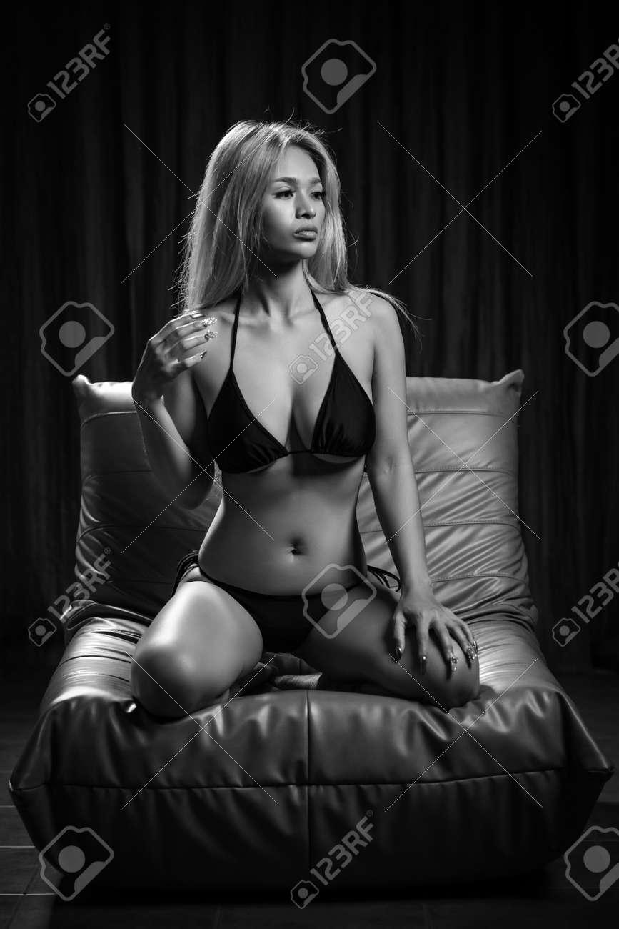 Sexy asian girl model in fancy black bikini is posing on the sofa - 167009587