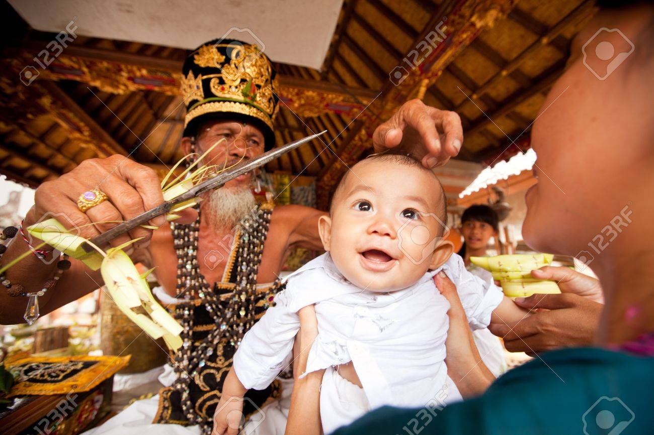 BALI, INDONESIA - MARCH 28: Unidentified child during the ceremonies of Oton - is the first ceremony for baby's on which the infant is allowed to touch the ground on March 28, 2012 on Bali, Indonesia. Stock Photo - 13161662