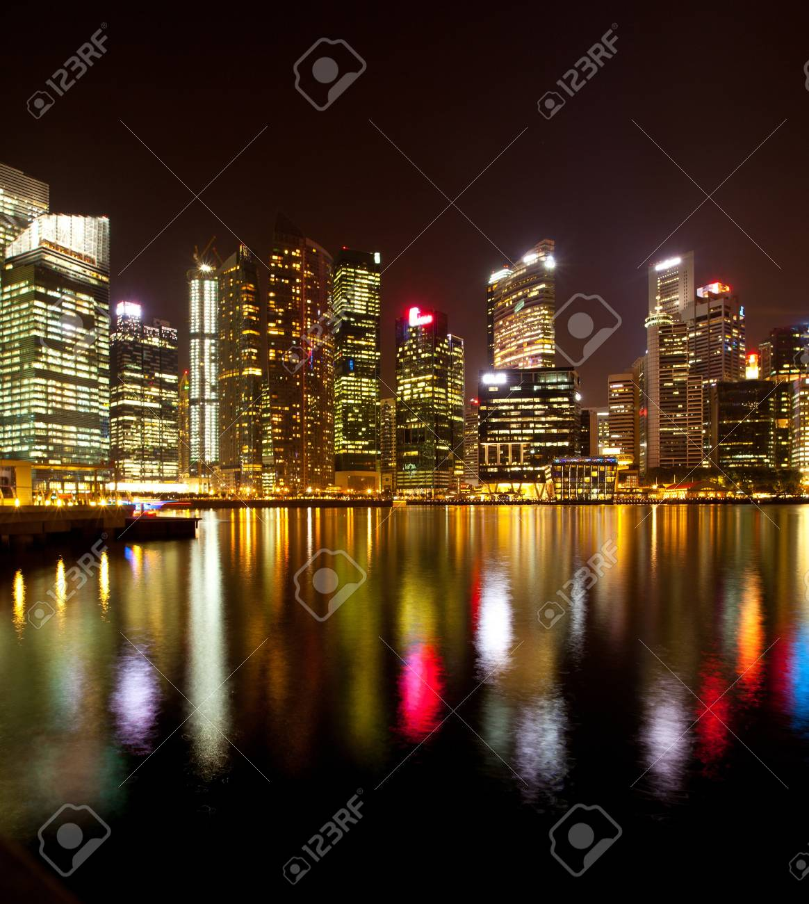 A view of Singapore business district, in the night time, with water reflections. Stock Photo - 14553685