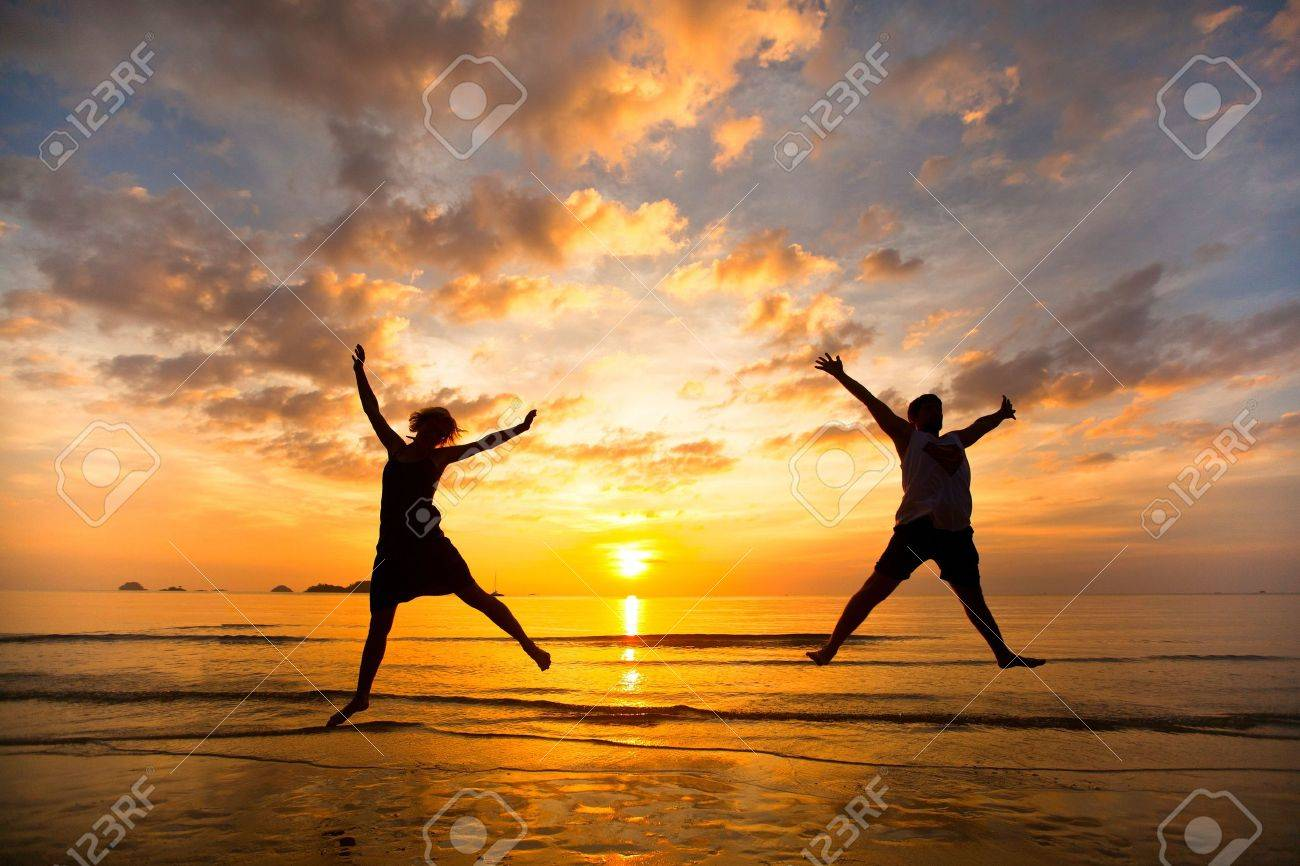 Young couple in a jump on the sea beach at sunset - 16693674