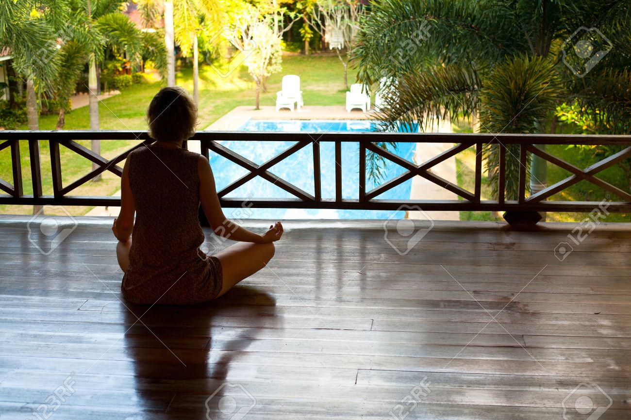 Young woman sitting in lotus position with the balcony looking at the pool in the spa resort Stock Photo - 16906318