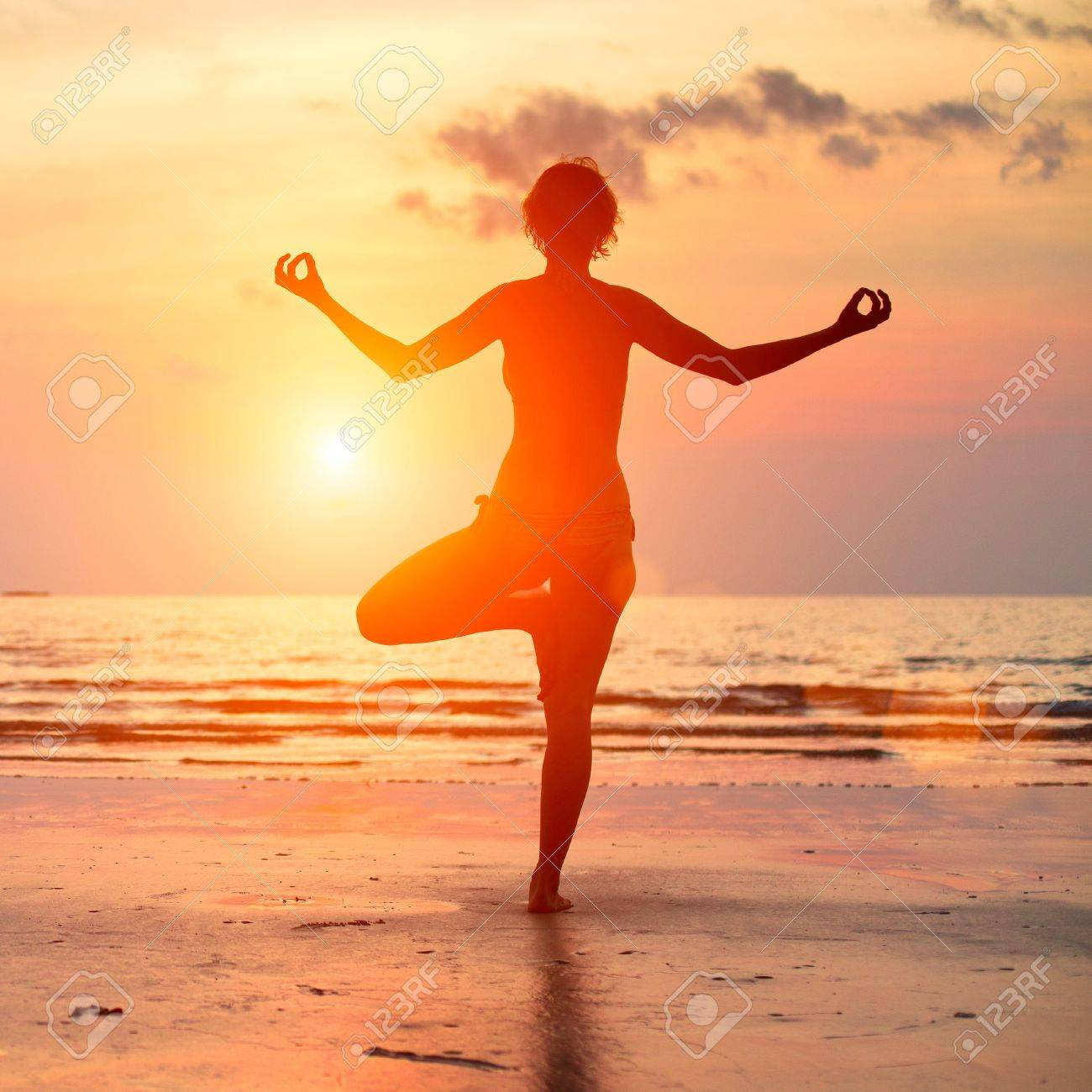 Silhouette of a beautiful yoga woman on the beach at sunset. Stock Photo - 17567279