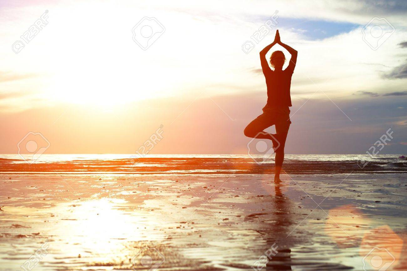 Young woman practicing yoga on the beach at sunset Stock Photo - 17667778