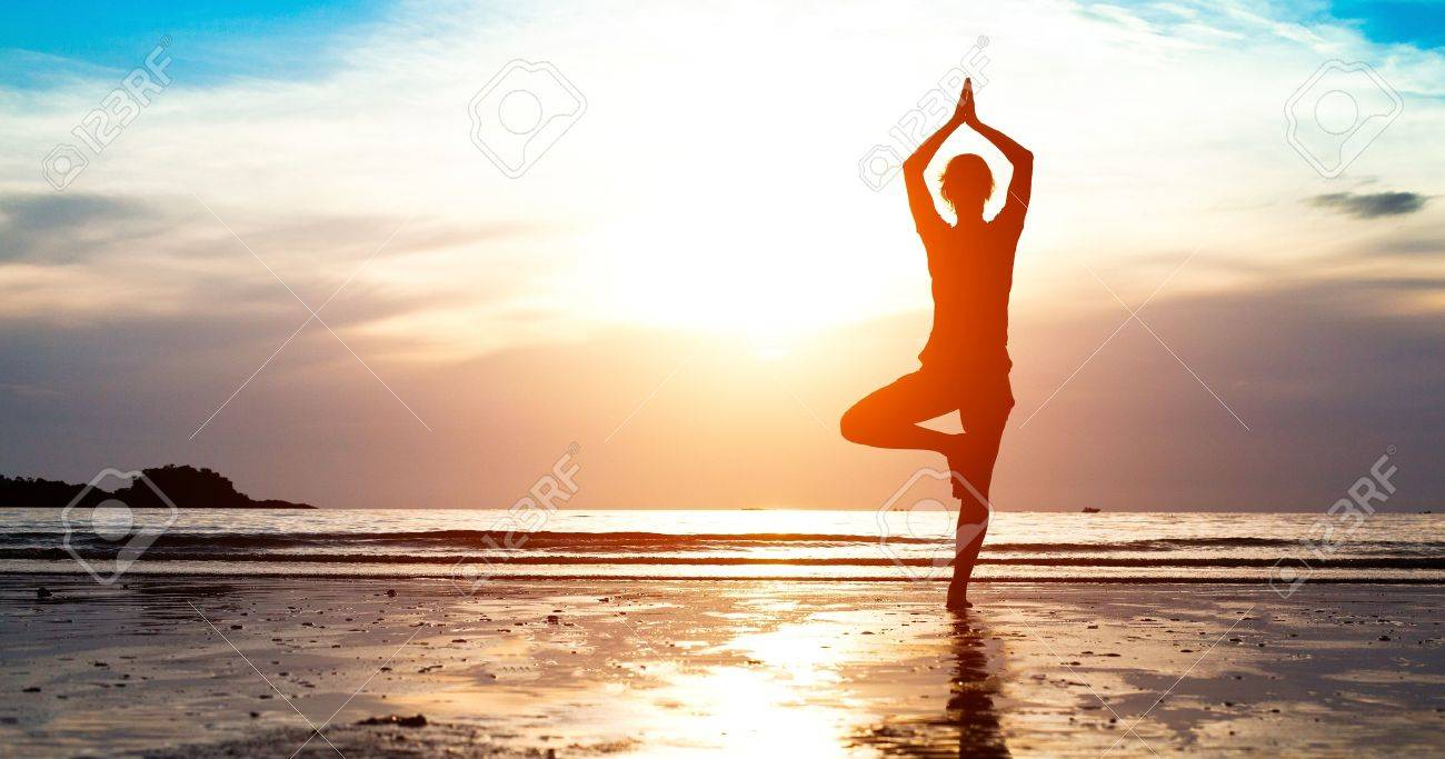 Silhouette young woman practicing yoga on the beach at sunset - 18715040