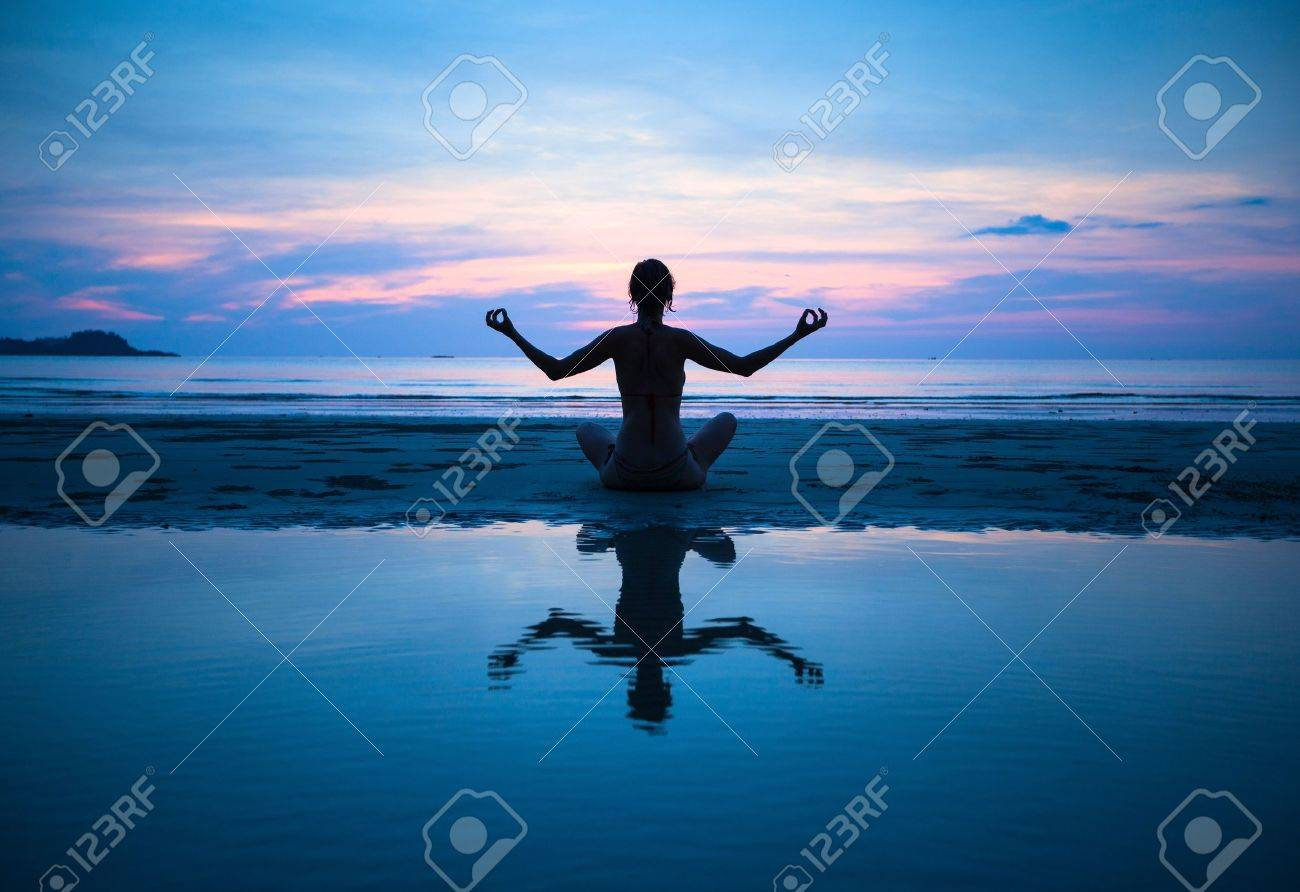 Woman practicing yoga on the beach at sunset (with reflection in water) Stock Photo - 18784343