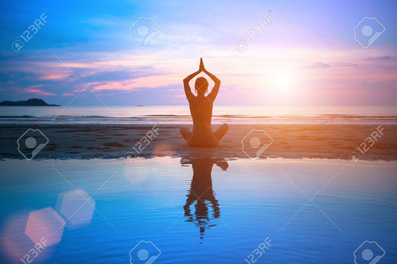 Silhouette young woman practicing yoga on the beach at sunset Stock Photo - 20573103