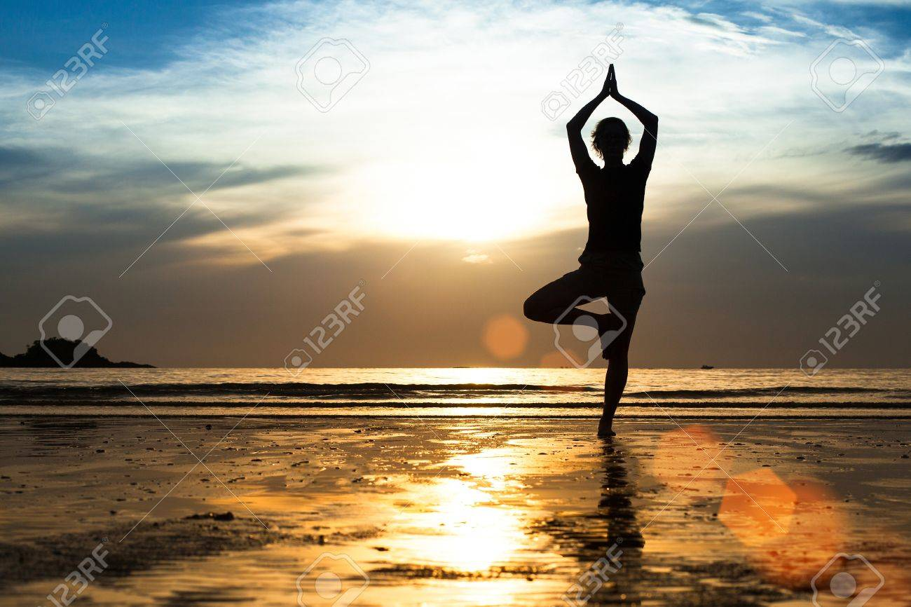 Silhouette of a young woman practicing yoga on the beach at sunset Stock Photo - 20699346