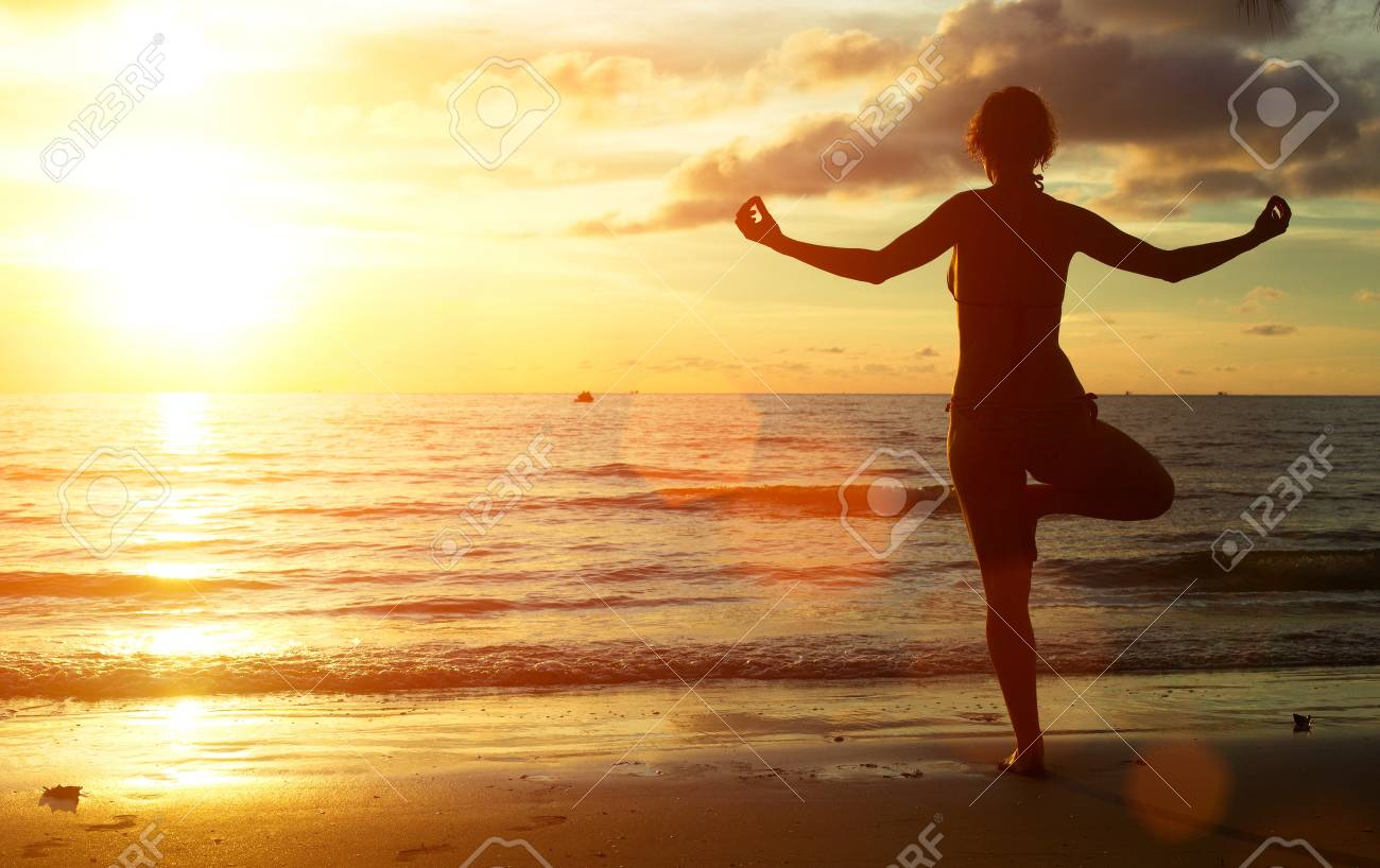 Yoga woman on the beach during sunset. Stock Photo - 22143155
