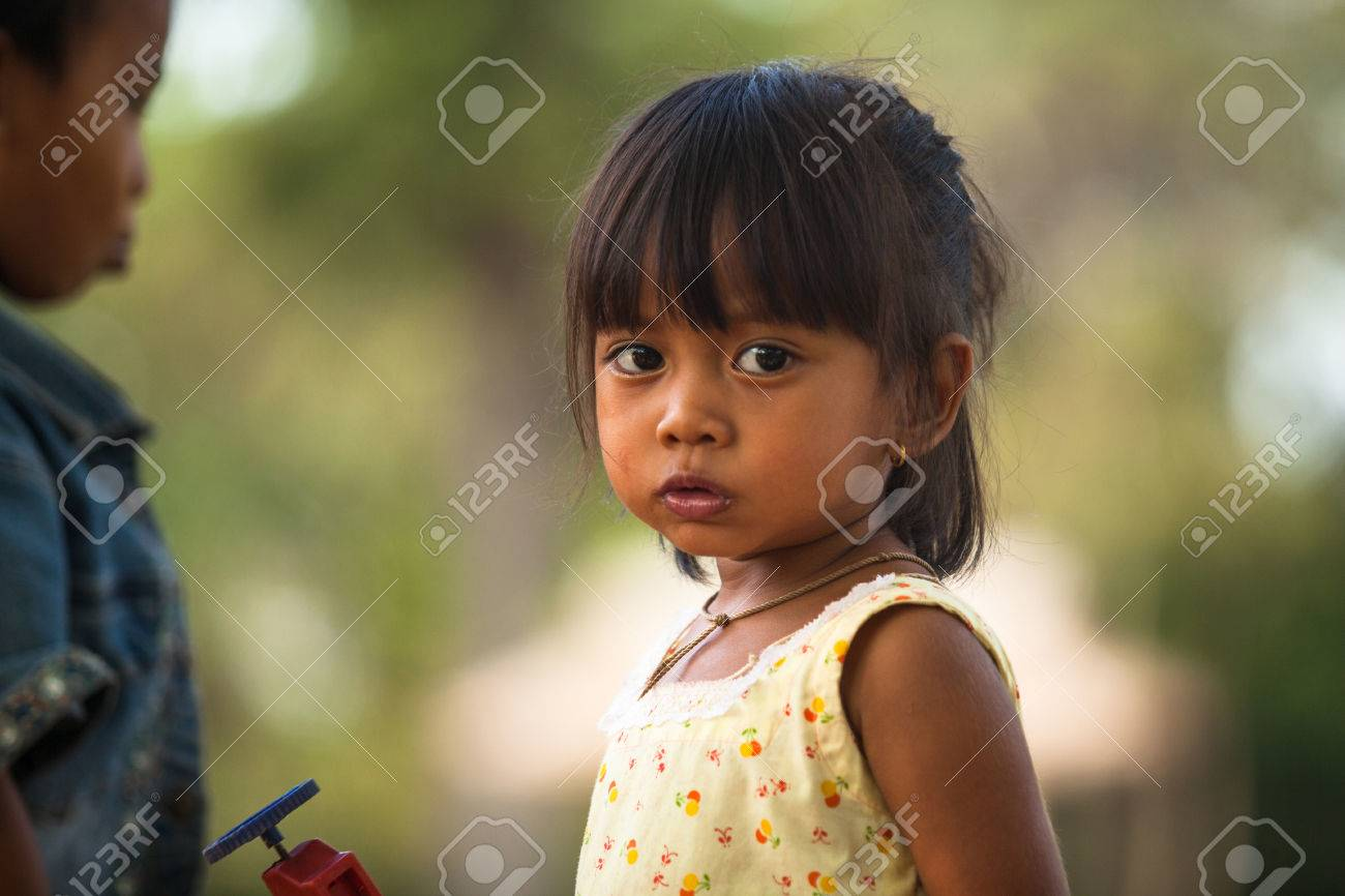 SIEM REAP, CAMBODIA - DEC 13: An unidentified poor child poses for tourists near Angkor Wat, Dec 13, 2012 on Siem Reap, Cambodia. Angkor Wat is the country's prime attraction for visitors.  Stock Photo - 22716239