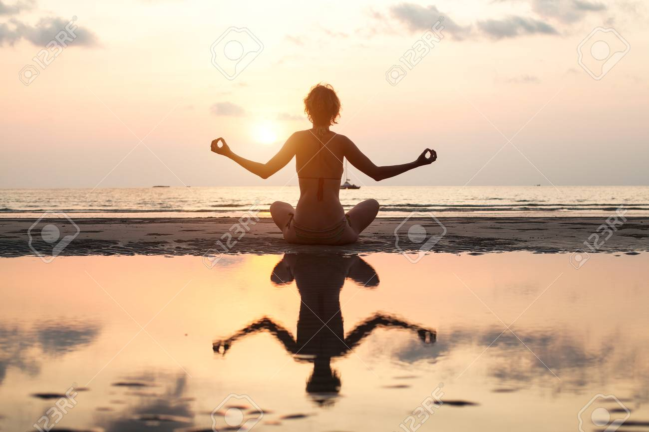 Yoga woman sitting in lotus pose on the beach during sunset, in bright colors, with reflection in water. Stock Photo - 23730290
