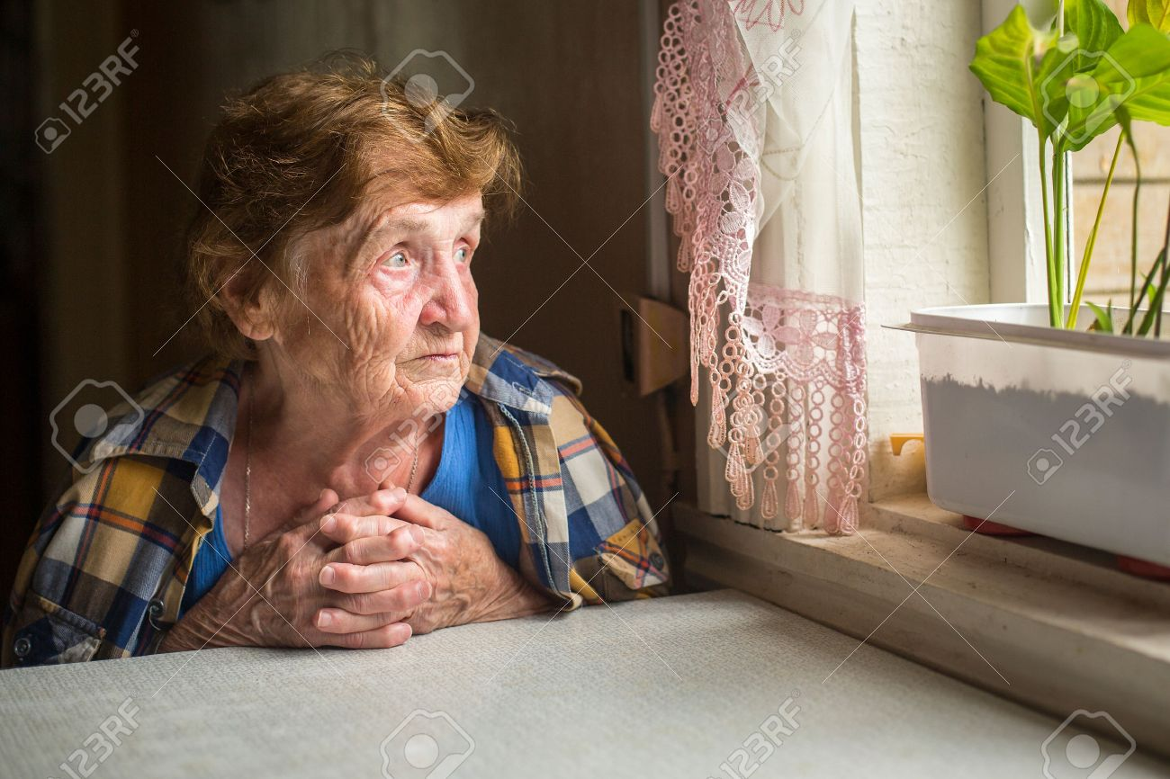Old lonely woman sitting near the window in his house. - 32704813