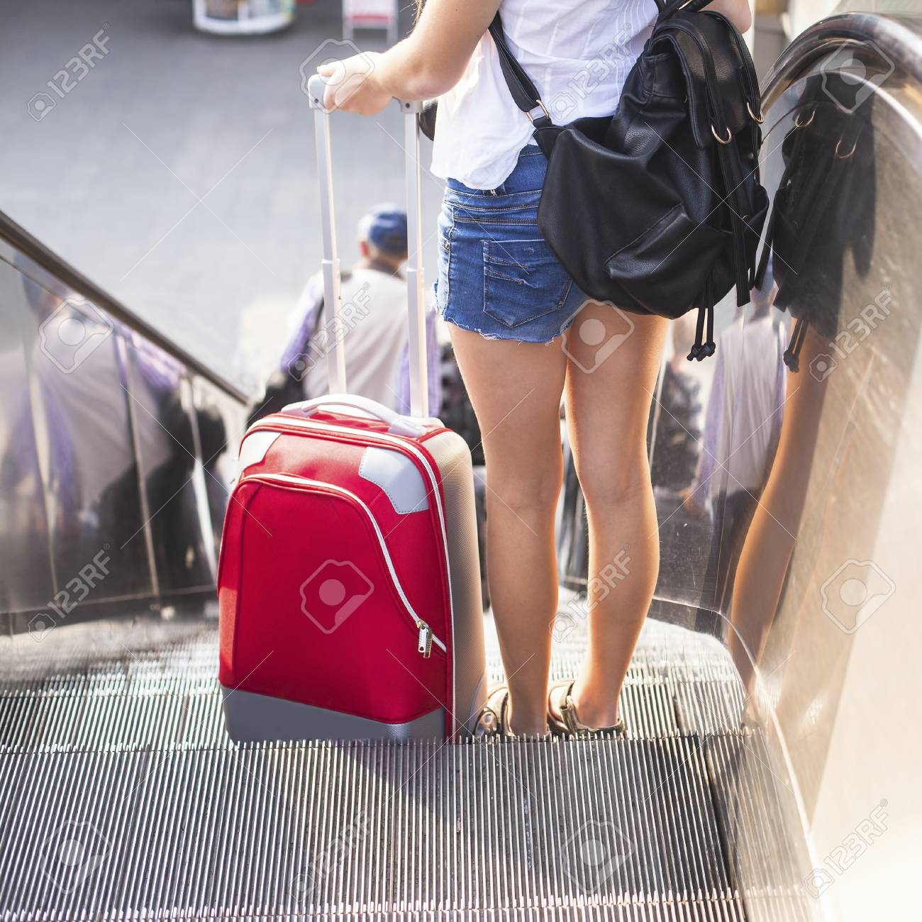 Young girl with the red suitcase standing on the escalator. Travel concept. - 37542855