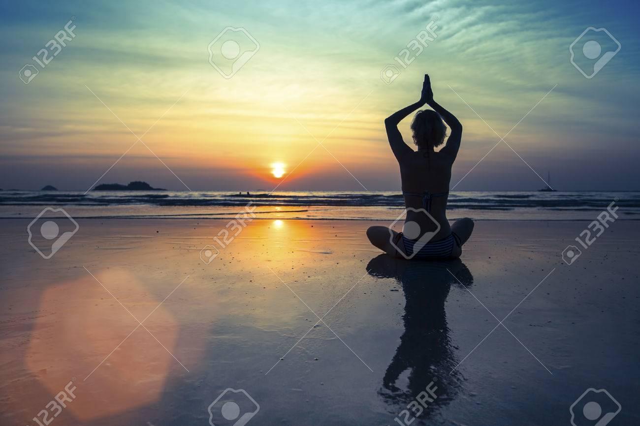 Female silhouette in Yoga meditation pose at amazing sunset. - 38677834
