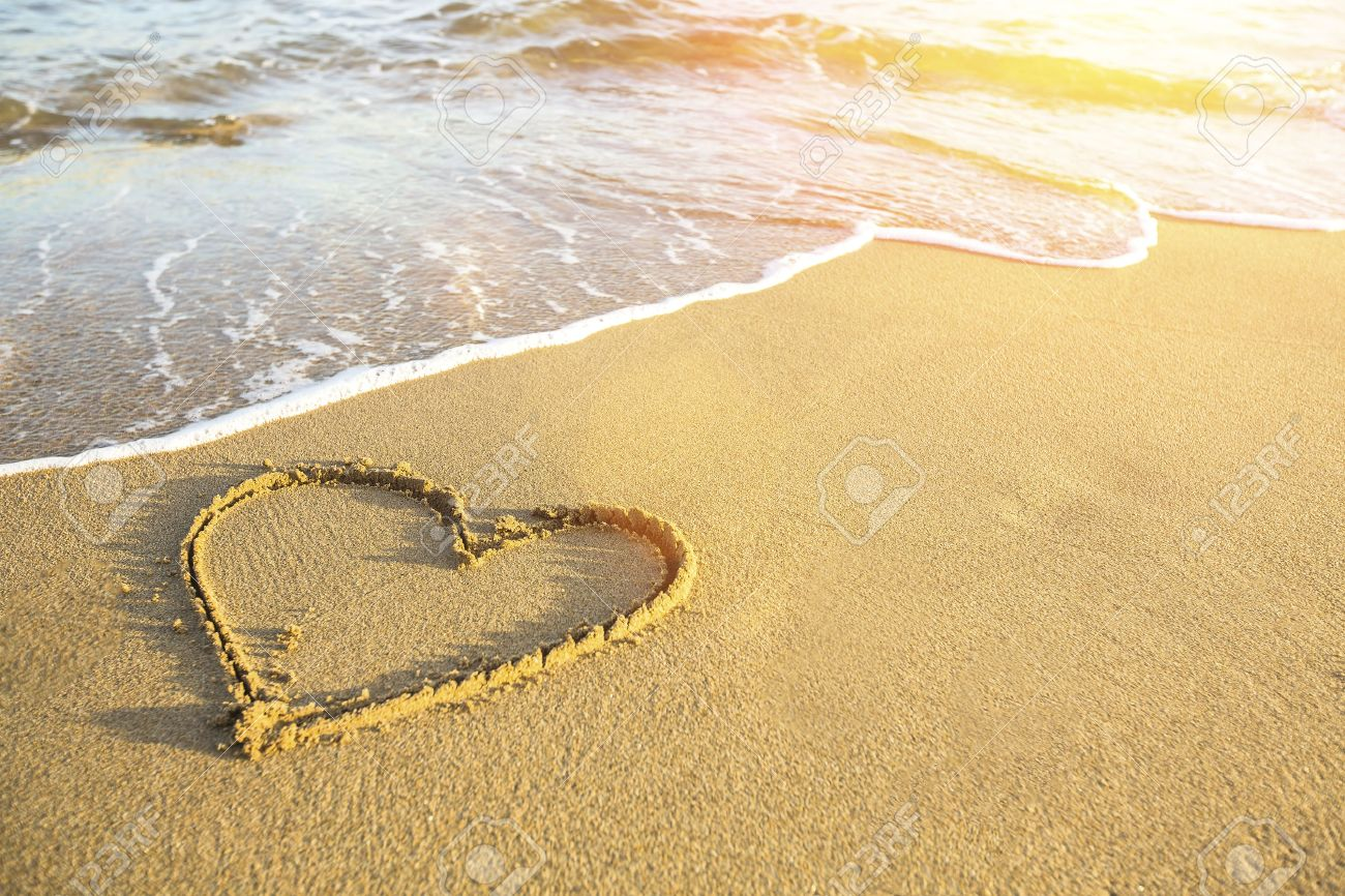 Heart drawn on the sand of a sea beach, soft wave and solar glare. - 39345304
