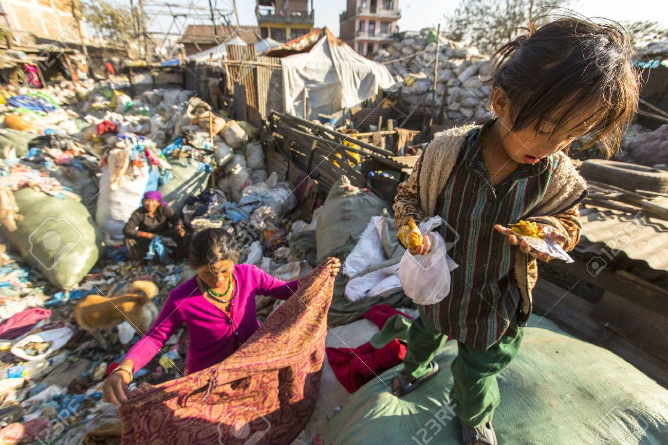 KATHMANDU, NEPAL - CIRCA DEC, 2013: Unidentified child and his parents during lunch in break between working on dump. Only 35% of population Nepal have access to adequate sanitation. - 39326288