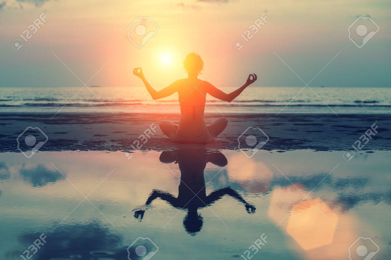 Silhouette meditation girl on the background of the stunning sea and sunset. Yoga, fitness and healthy lifestyle. - 39575631