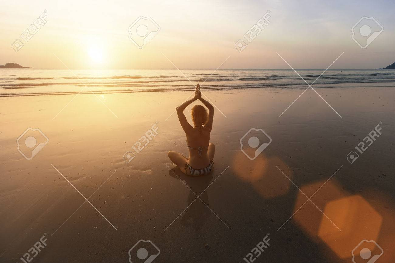 Beautiful girl sitting on the beach during sunset and meditating in yoga pose. - 39950259