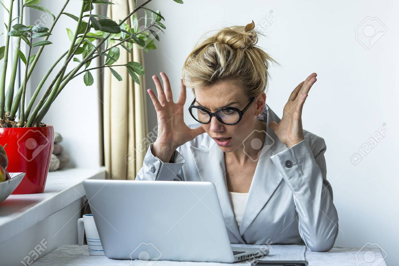 Business woman in a state of shock sitting near the computer. - 43393032