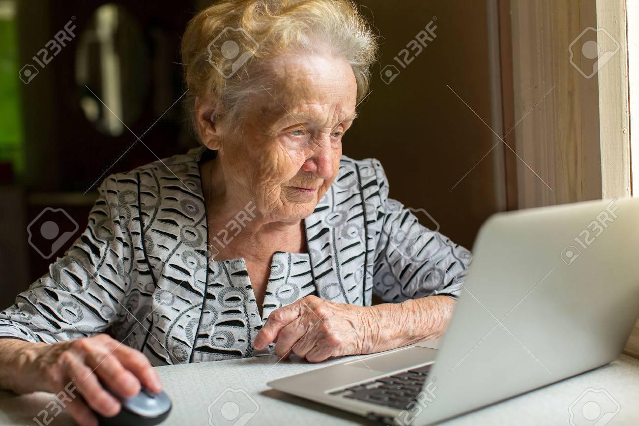 An elderly woman working on a laptop. - 44814472