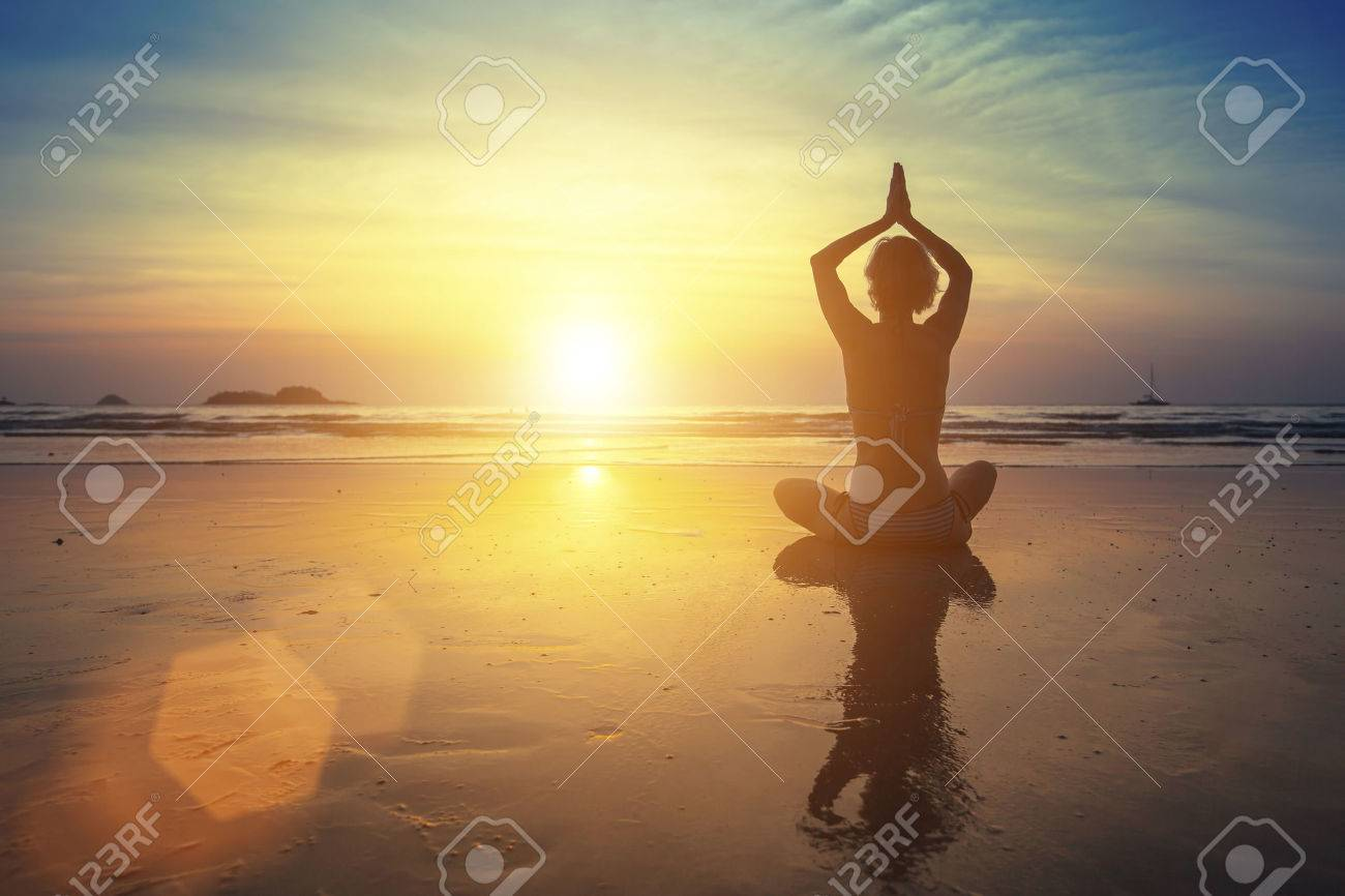 Young woman practicing yoga on the beach at amazing sunset (with reflection) - 44814476