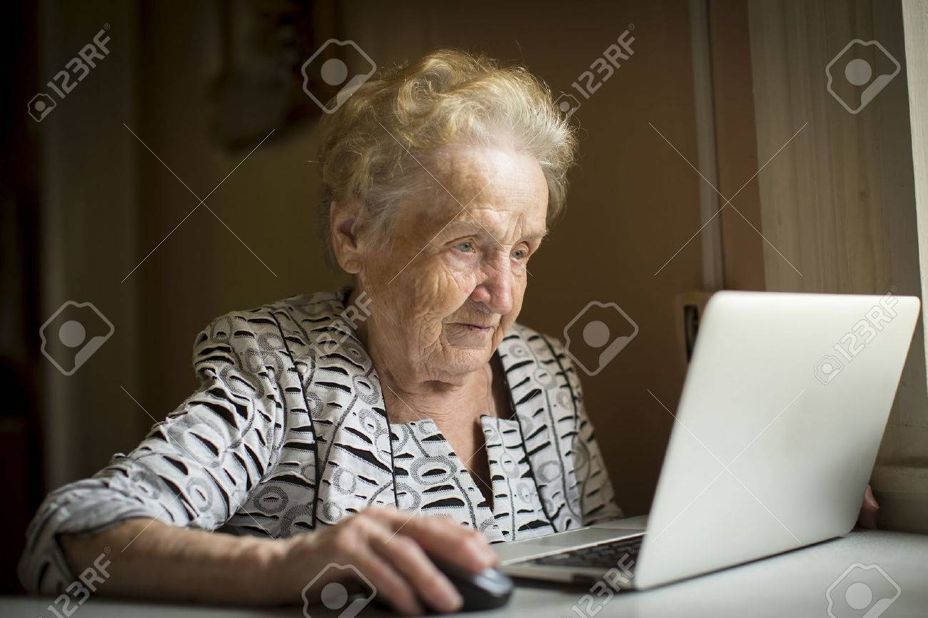 Old woman sitting with laptop at table in his house. - 45393059