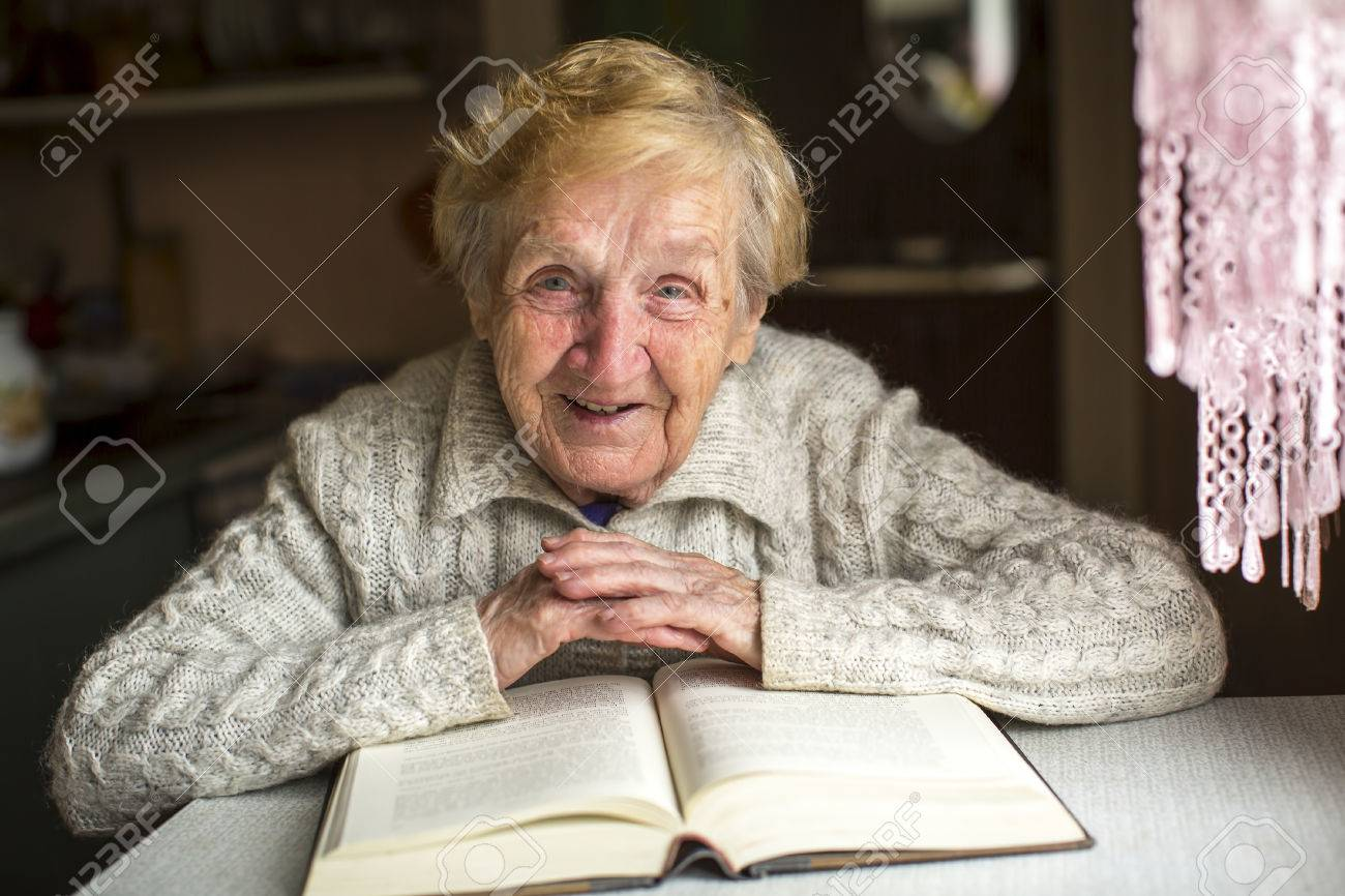 An elderly woman sits with a book at the table. - 48954949