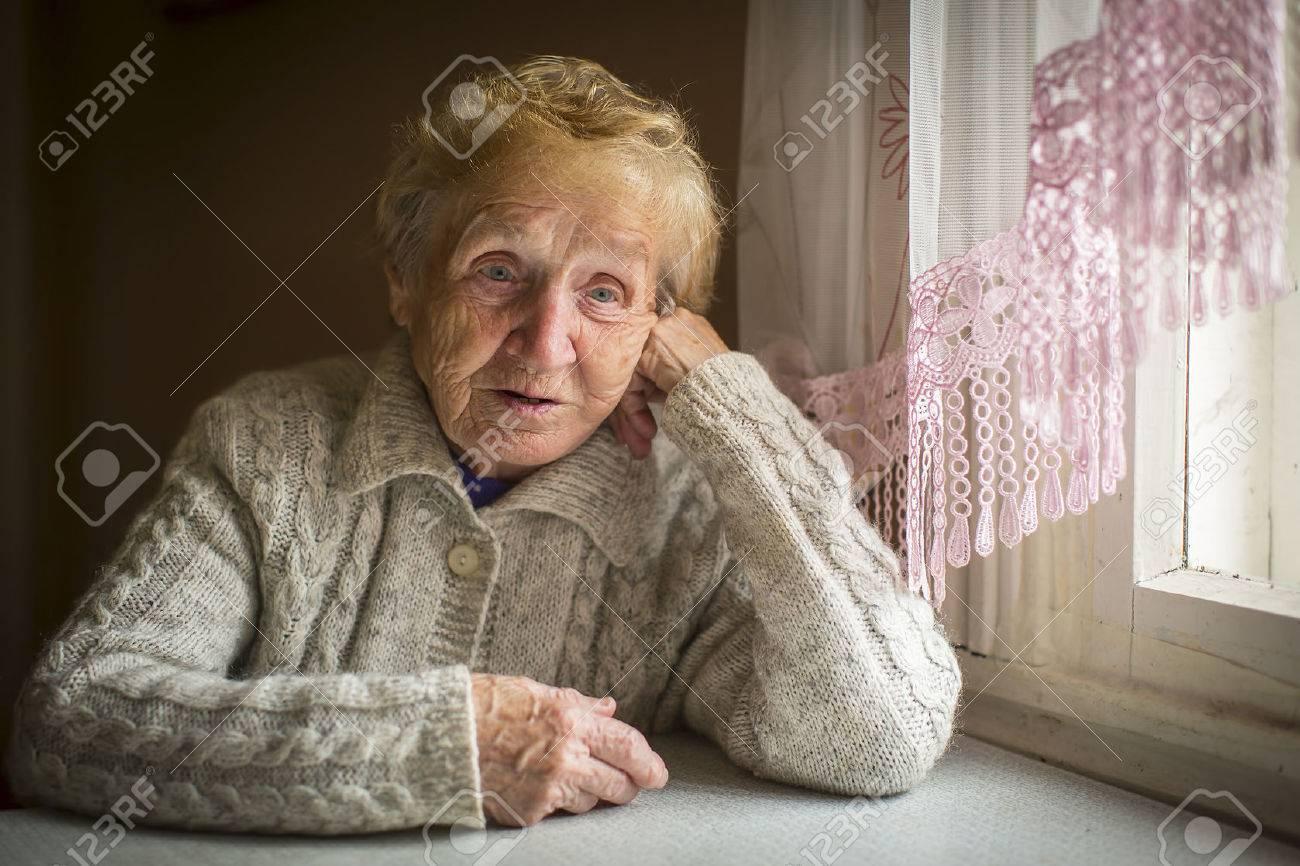 An elderly woman sits alone near the window. - 49489275