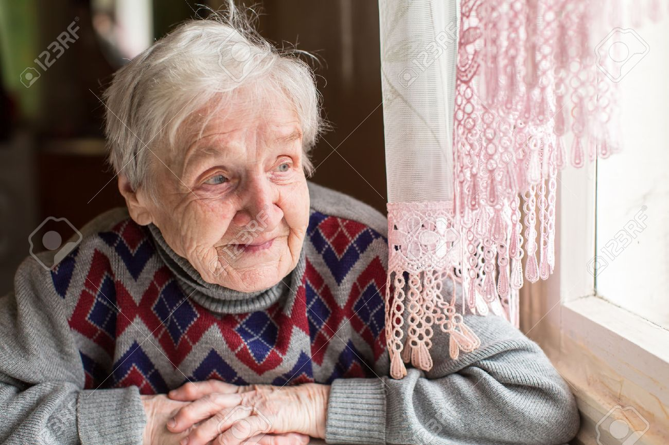 An elderly woman, a grandmother, with a smile looking out the window sitting in the kitchen. - 56494667