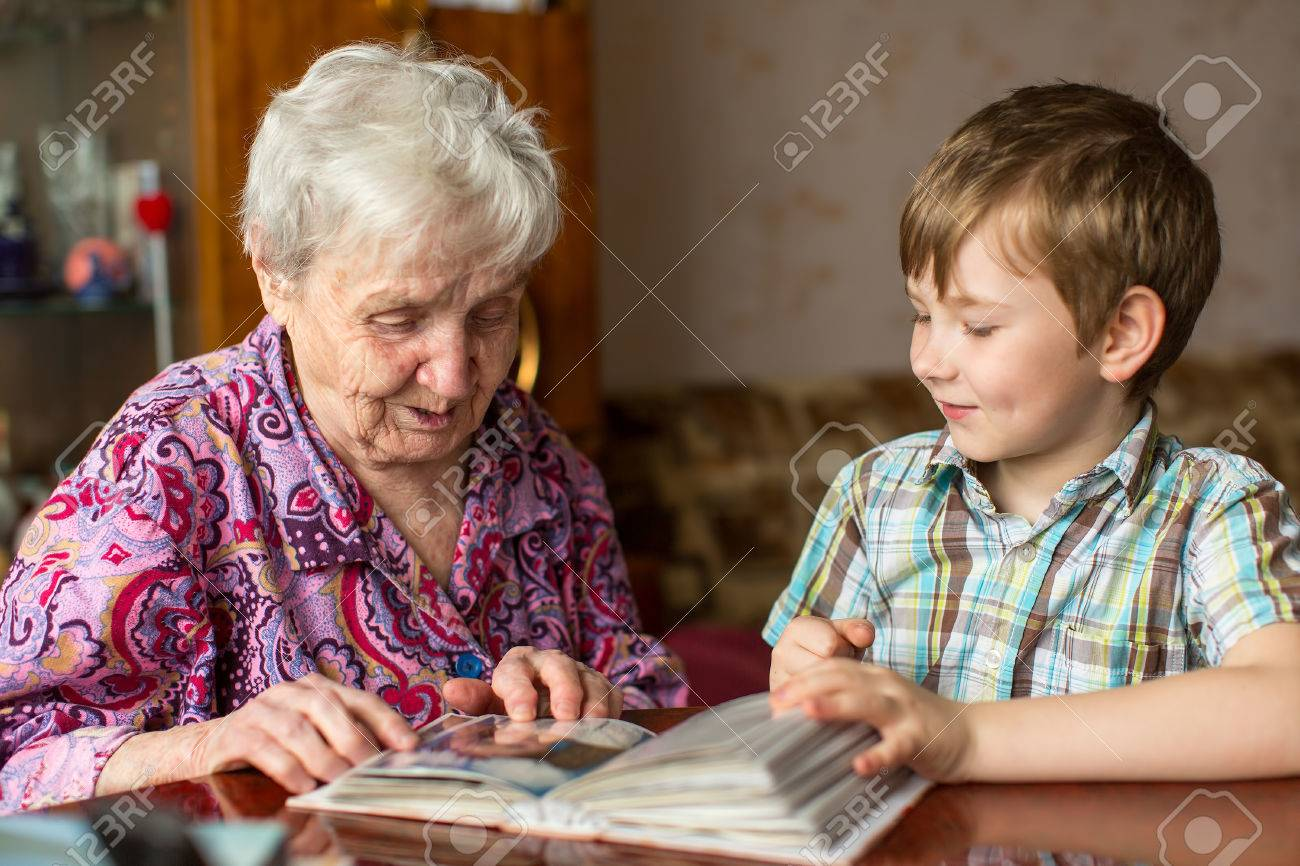 Grandmother and grandson looking photo album. - 57049000
