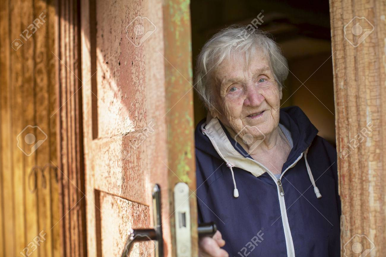 An elderly woman opens the door of the house. - 57102886