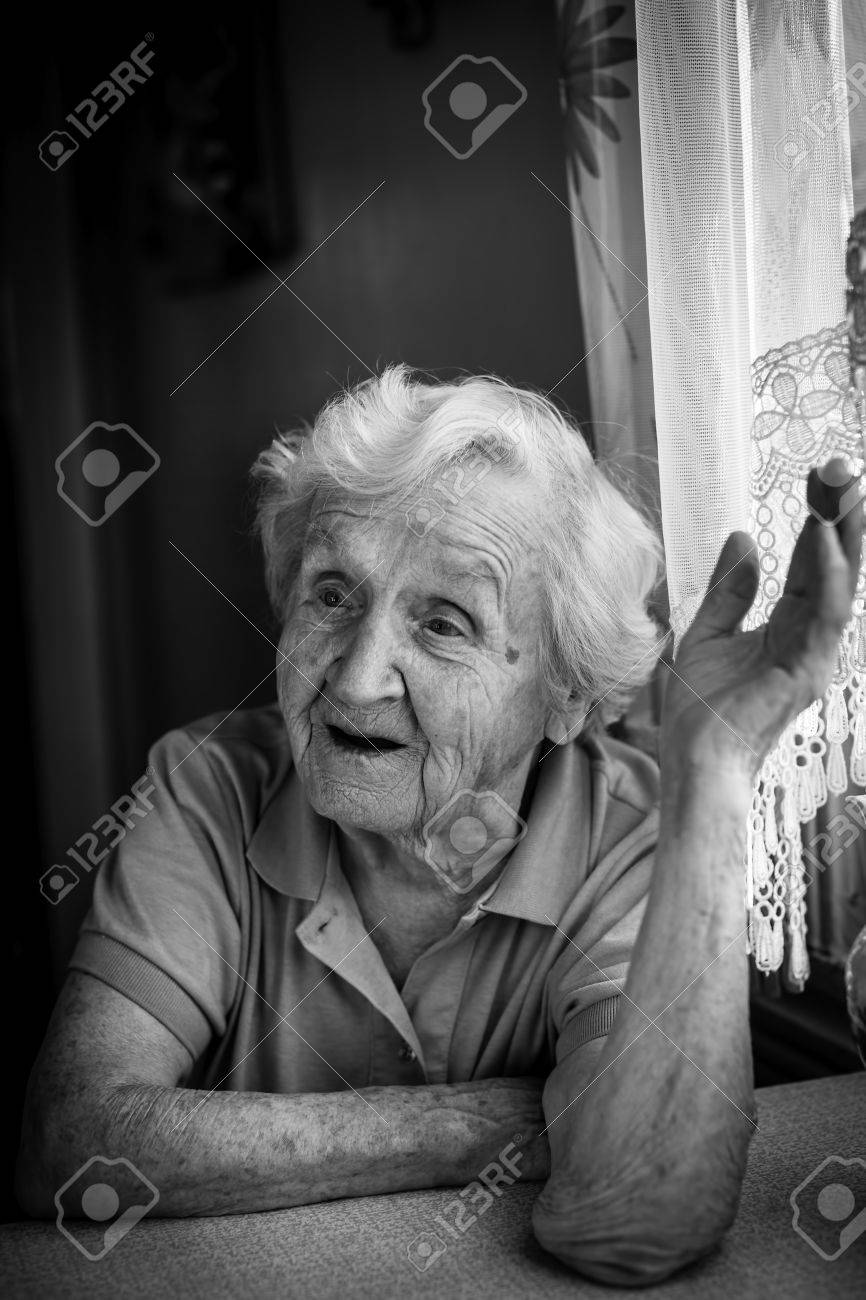 Black and white portrait of an old woman talking in the house stock photo