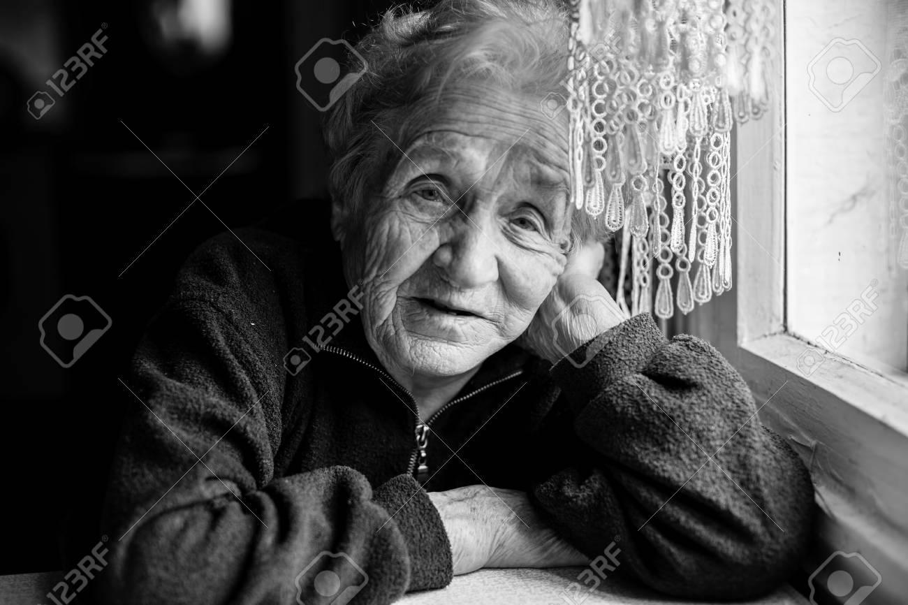 Sad elderly woman sitting near the window black and white photo stock