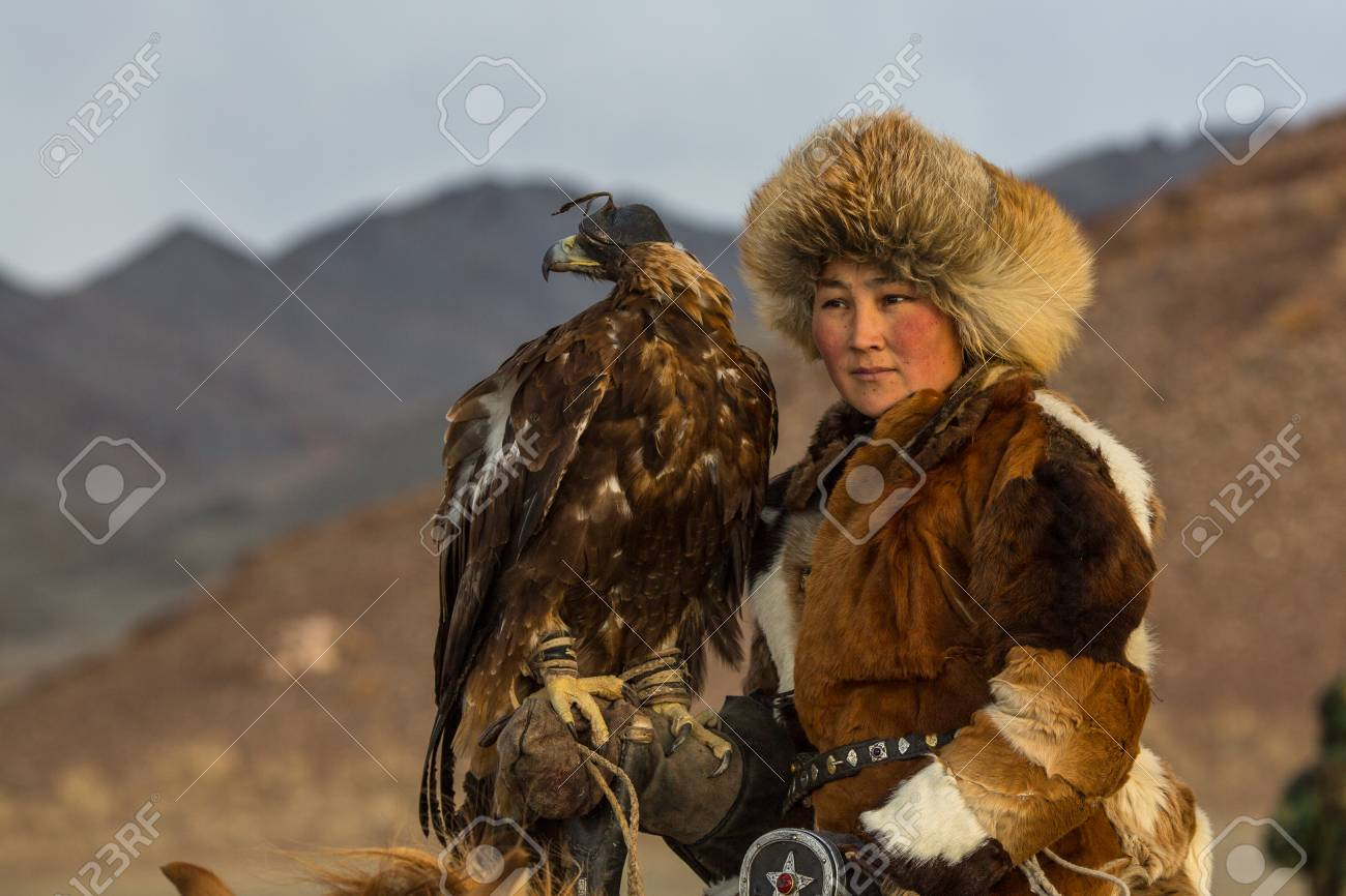 SAGSAY, MONGOLIA - SEP 28, 2017: Young woman Eagle Hunter at traditional clothing, while hunting to the hare holding a golden eagles on his arms in desert mountain of Western Mongolia. - 91157600