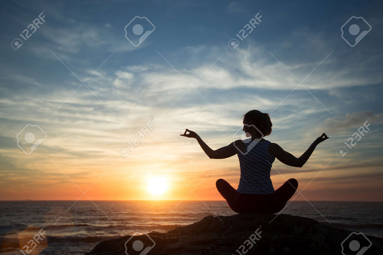 Silhouette young woman practicing yoga on the beach at sunset. - 125107716