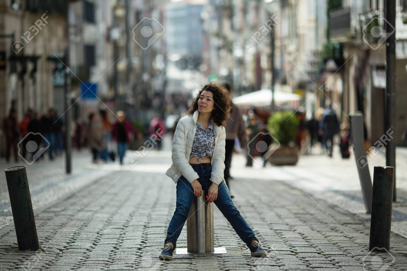 Young asian mixed-race woman is posing on the St. Catarina street, Porto, Portugal. - 143009396
