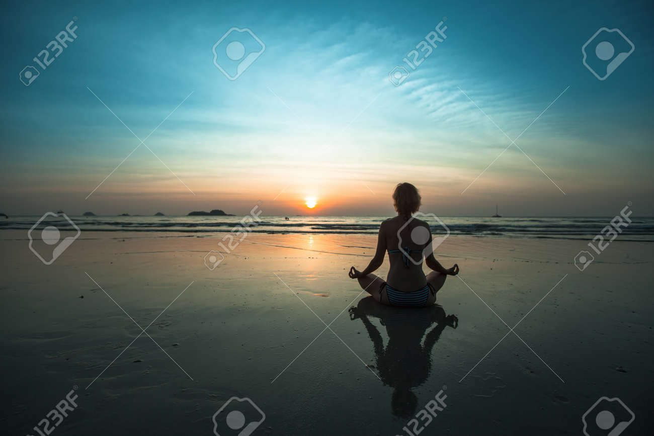 A woman sitting on beach during sunset and meditating at yoga pose. - 168017759
