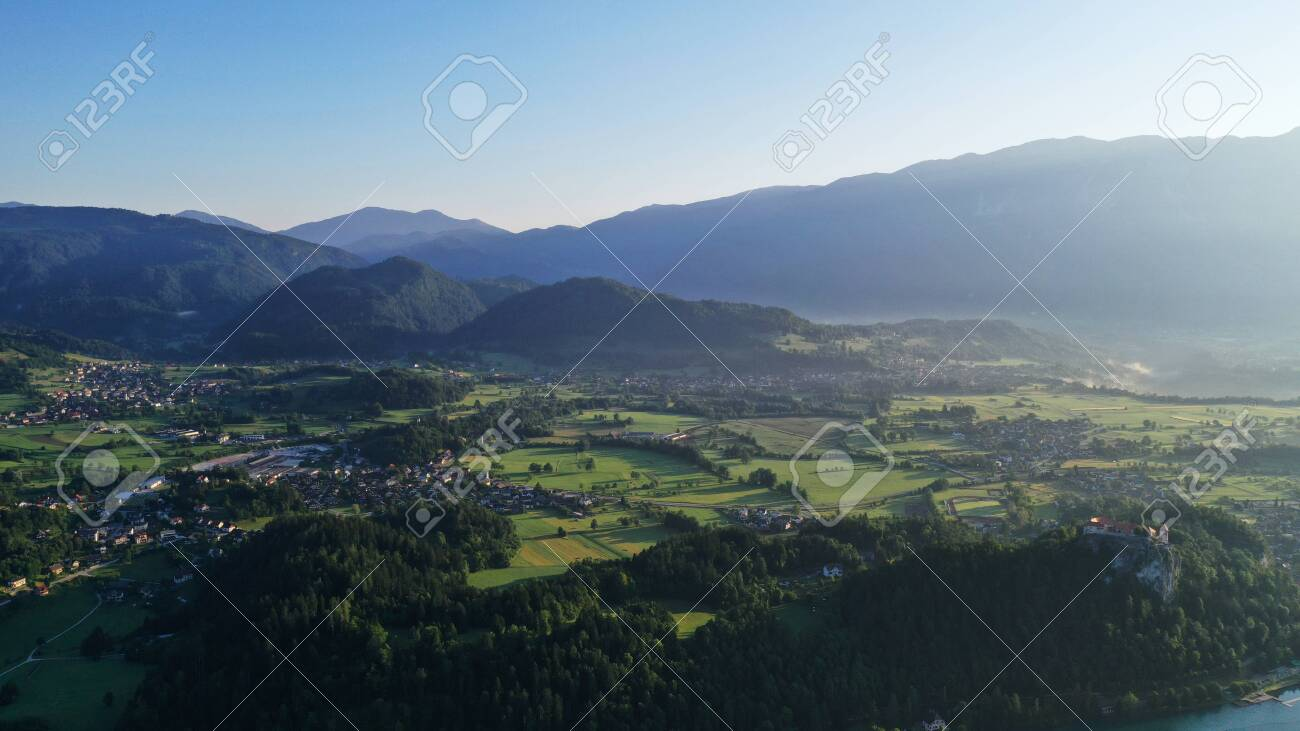 Aerial view of Bled Lake valley. Natural landscape with green meadows, fields, hills and mountains, small houses and trees. Sunny blue sky. Sun rays. - 139935514