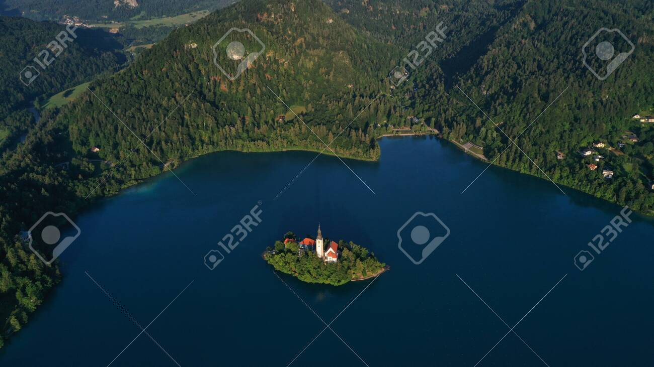 Aerial view of small island with Church of assumption of Mary in the middle of Lake Bled, Slovenia. Summer. Green Mountains landscape around lake. - 140685954