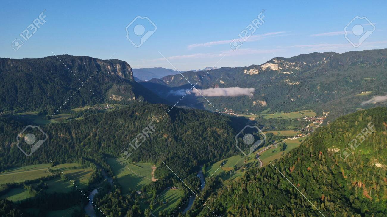 Aerial view of Bled Lake valley. Natural landscape with green meadows, fields, hills and mountains, small houses and trees. Sunny blue sky. Sun rays. - 140685961