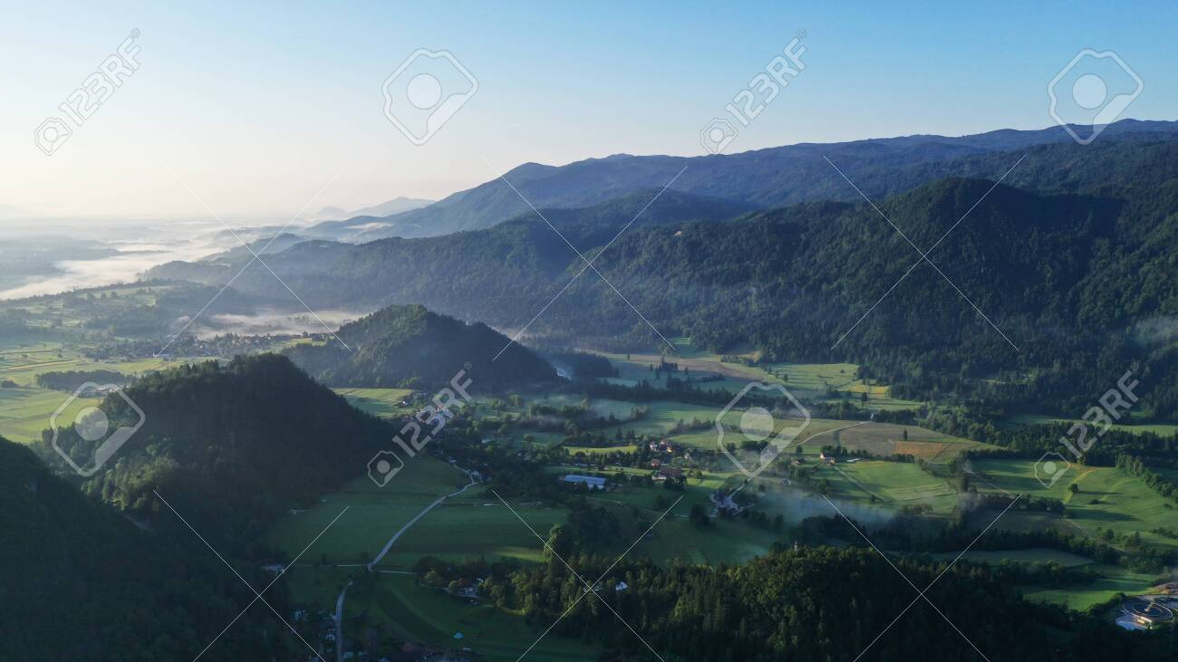 Aerial view of Bled Lake valley. Natural landscape with green meadows, fields, hills and mountains, small houses and trees. Sunny blue sky. Sun rays. - 141440845