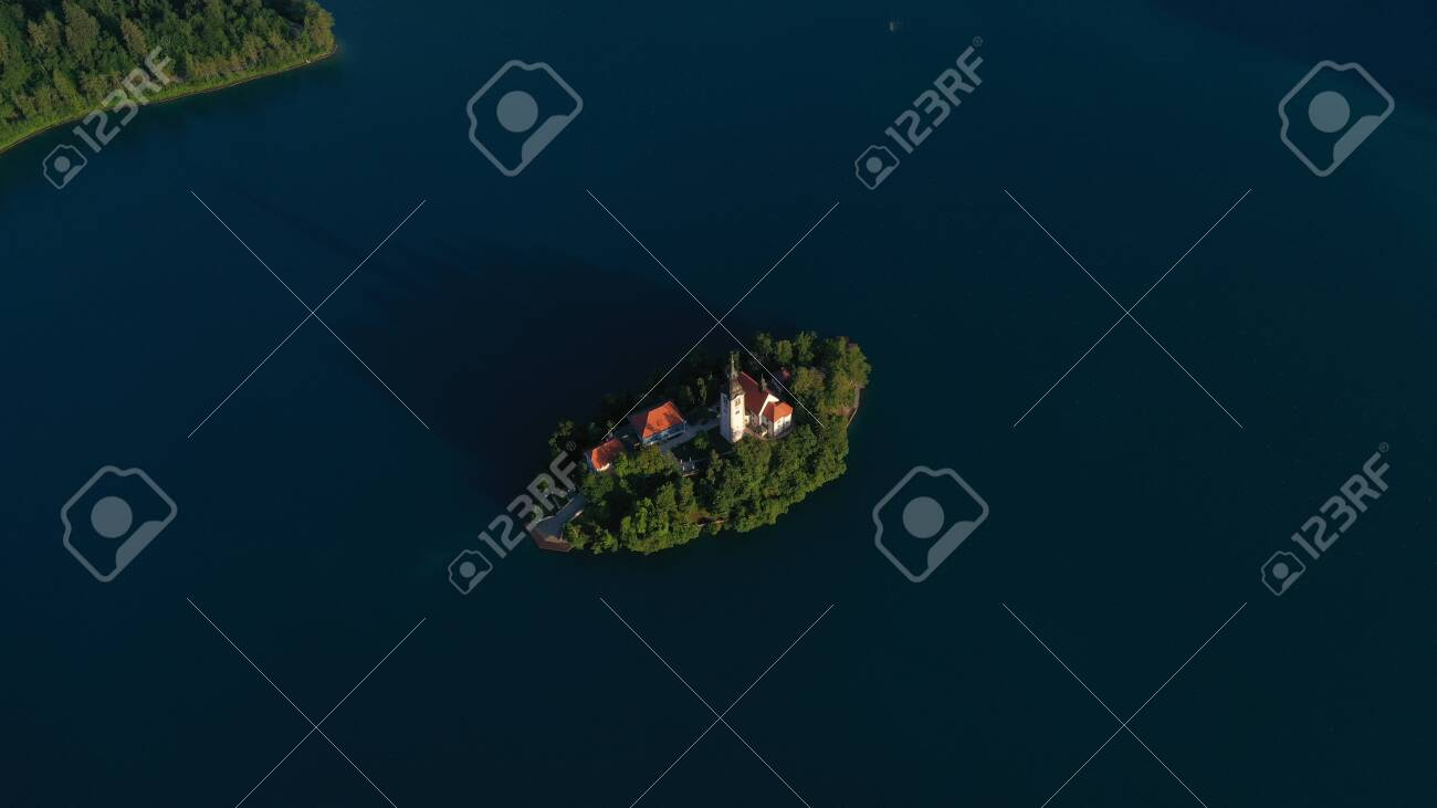 Aerial view of small island with Church of assumption of Mary in the middle of Lake Bled, Slovenia. Summer. Green Mountains landscape around lake. - 141440858