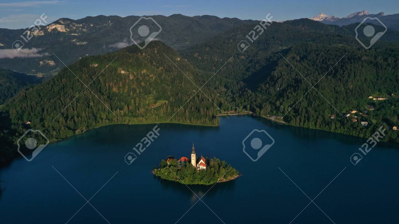 Aerial view of small island with Church of assumption of Mary in the middle of Lake Bled, Slovenia. Summer. Green Mountains landscape around lake. - 141440931