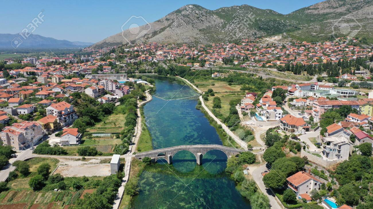 Aerial view of Arslanagic`s bridge on Trebisnjica river in Trebinje Old Town. Bosnia and Herzegovina. Summer sunny day, Turquoise water, mountains, trees, blue sky, small houses. - 139903391