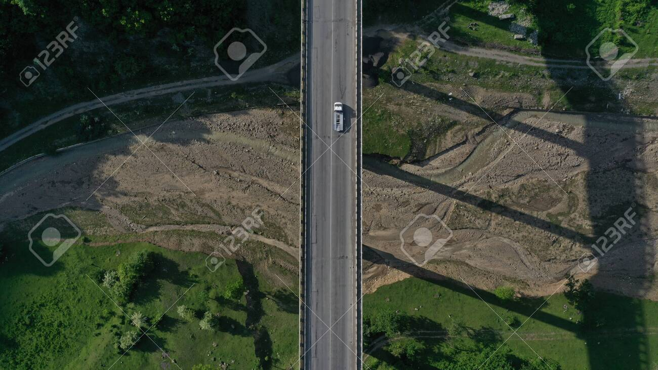 Aerial top down view of bridge over Aragvi river near Ananuri Fortress and Church. Mountain landscape. Summer. Green trees. Cars going on bridge road. Georgia. - 138810957