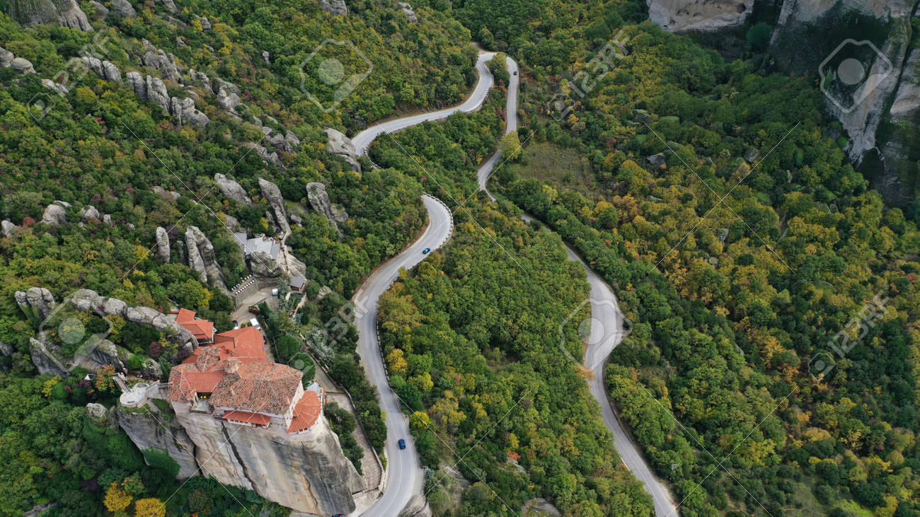 Aerial view of winding road near monastery on the cliff, Meteora mountains valley, Kalampaka, Greece. - 140592676