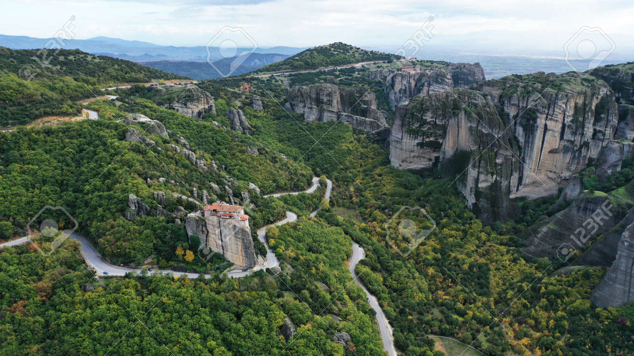 Aerial view of winding road near monastery on the cliff, Meteora mountains valley, Kalampaka, Greece. - 140592755