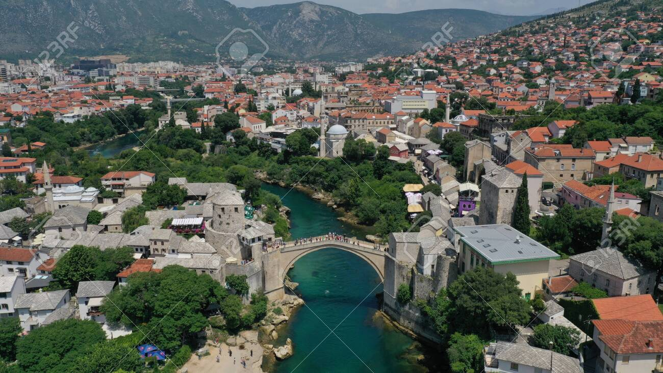 Aerial view of Stari Most old medieval bridge in Mostar, Neretva river, Bosnia and Herzegovina. Tourists walking on the bridge. Summer landscape of old town. Mosque on background. - 139967239